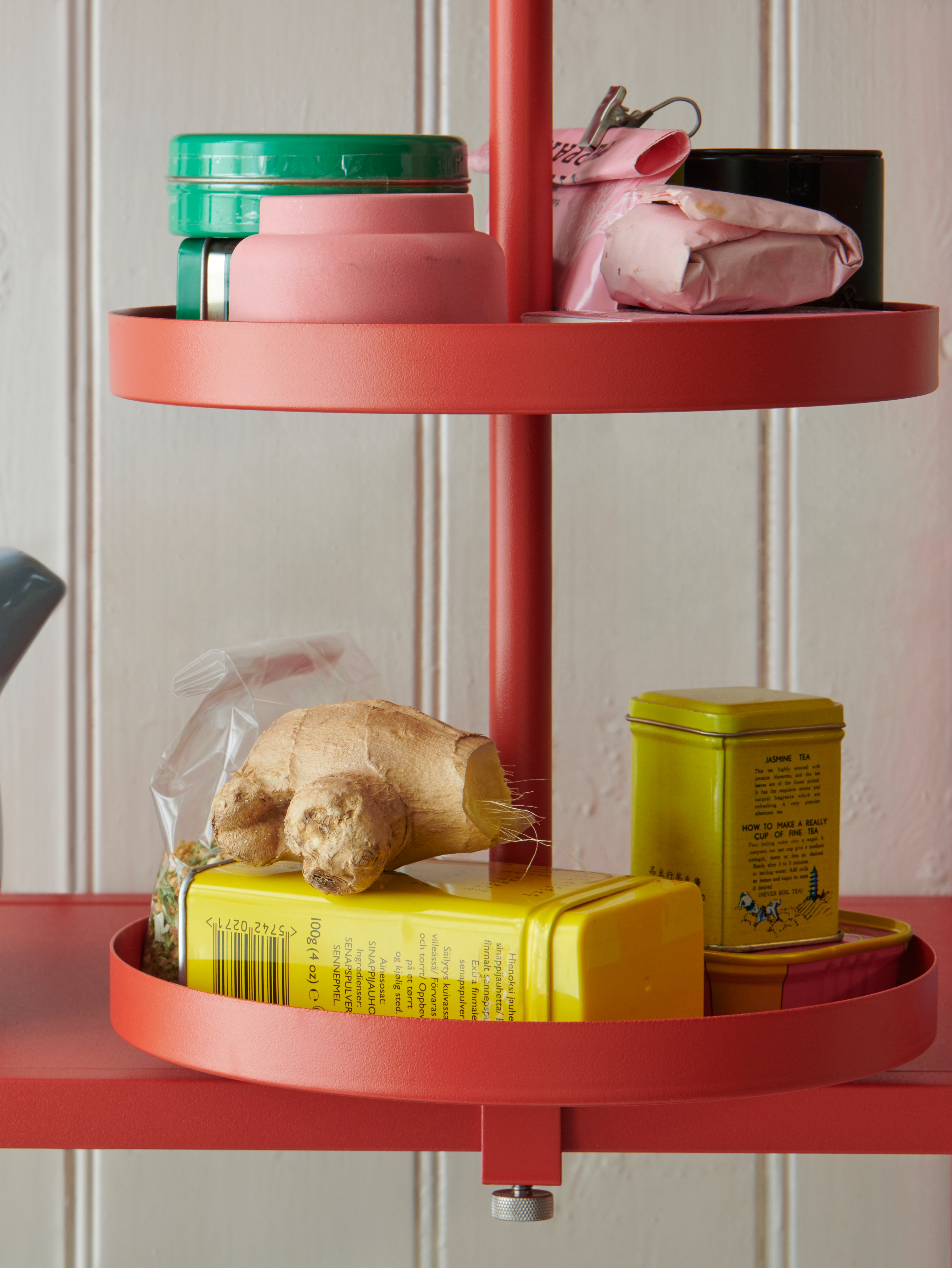 A red-orange ENHET swivel shelf filled with small cans and containers, fastened to an ENHET shelf.