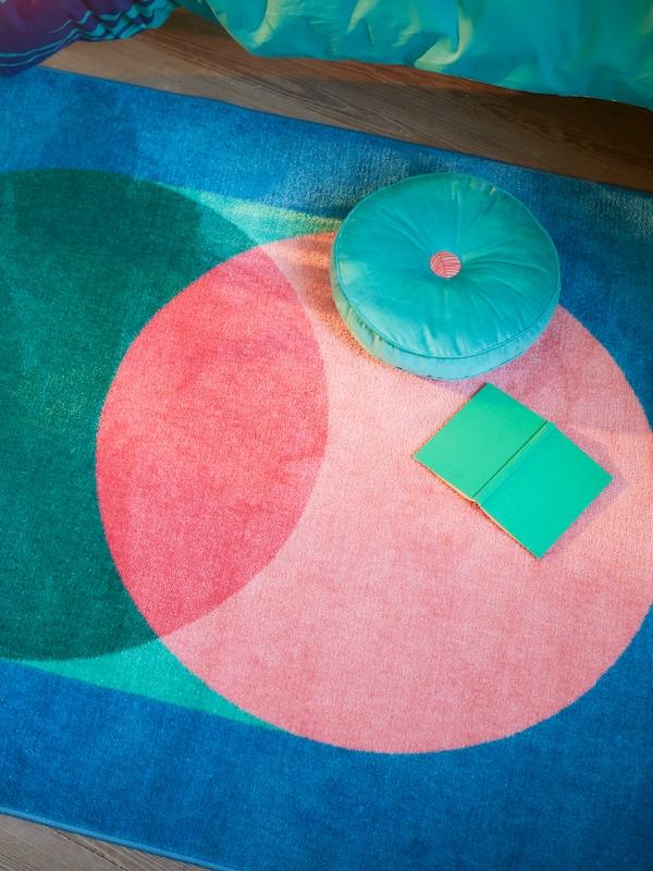 Un tapis GRACIÖS avec un grand motif circulaire en rose et vert sur fond bleu, avec un livre et un coussin posés dessus.