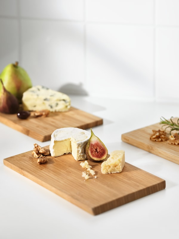Three APTITLIG chopping boards on a white surface, each holding various types of cheese and fruit, including figs and pears.