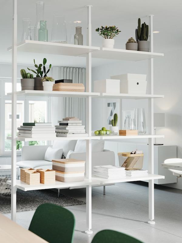 Hvidt opbevaringssystem brugt som rumdeler. På hylderne står der dekorative ting, planter, bøger og opbevaringskasser.
