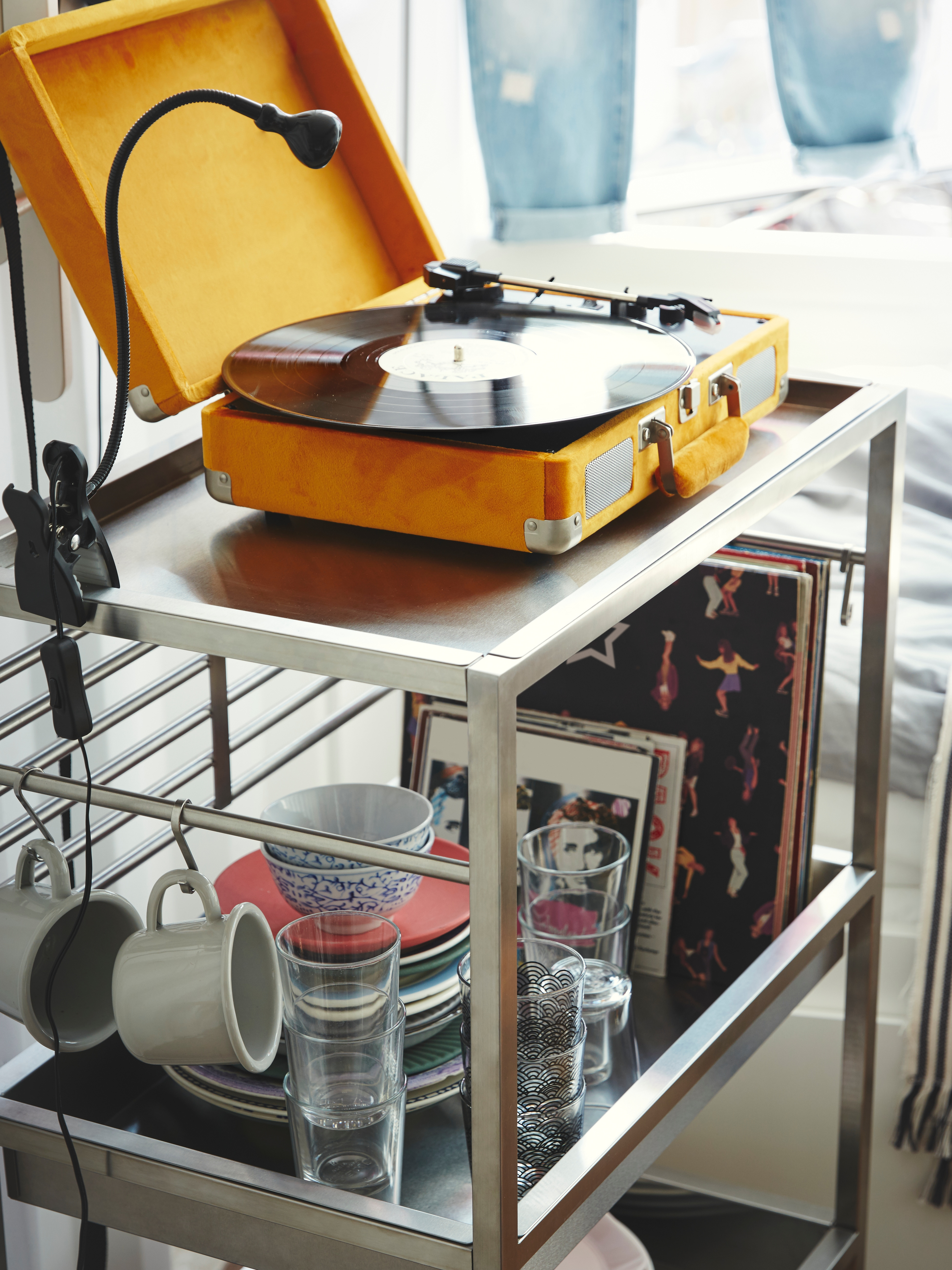KUNGSFORS trolley with yellow turntable and spot light on top shelf, and records and crockery on the shelf below.