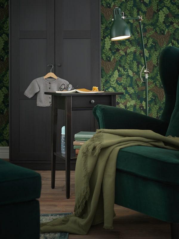 Un spațiu de lectură cu un scaun cu brațe verde, un lampadar verde și o noptieră HEMNES pe post de măsuță de cafea.