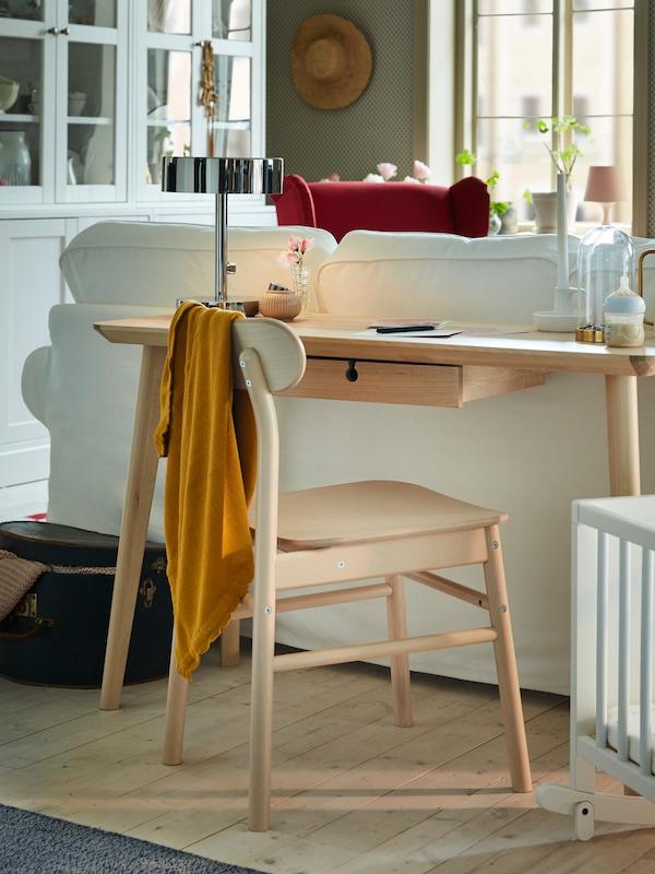 Kőris furnér LISABO íróasztal és egy nyírfa szék egy fehér kanapé mögött, a háttérben fehér üvegajtós szekrénnyel.