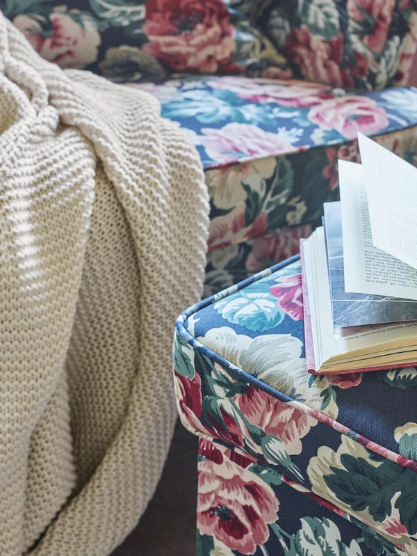 Light coloured INGABRITTA throw draped over the edge of a floral patterned sofa, near a footstool with an open book on it.