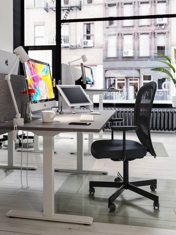 Sedia da ufficio nera, scrivanie regolabili in altezza, computer con sfondo desktop colorato, tazza di caffè, smartphone.