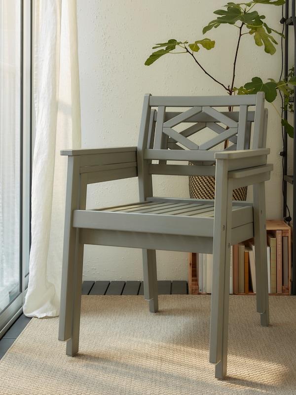 Zwei graue BONDHOLMEN Armlehnstühle übereinander gestapelt vor einem Regal an einer Wand