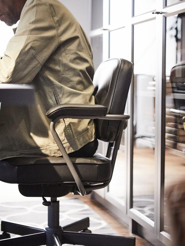 Homme assis sur une chaise pivotante ALEFJÄLL devant une bibliothèque BILLY.