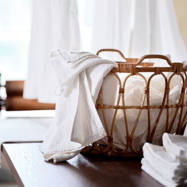 A rattan SNIDAD basket containing clean laundry sits on top of a brown stained oak veneer MÖRBYLÅNGA table.