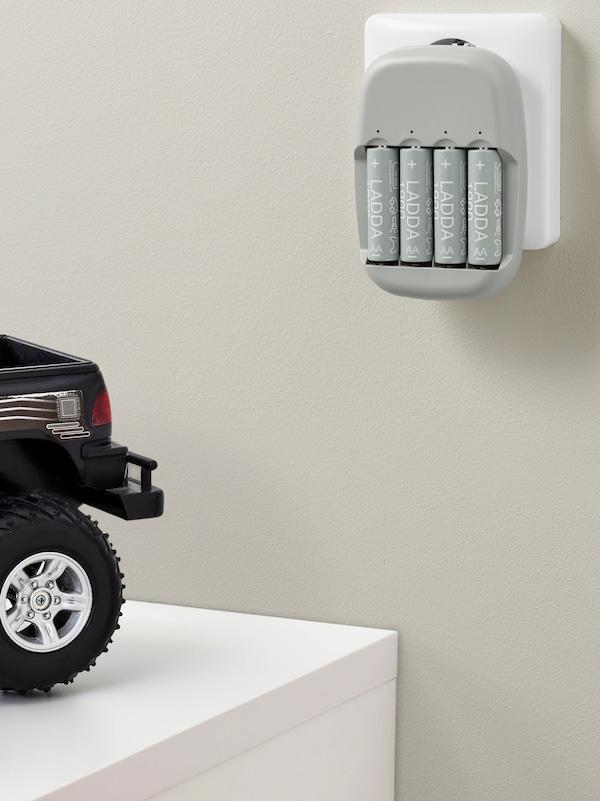 Un caricabatterie STENKOL inserito in una presa a muro ricarica quattro batterie ricaricabili LADDA vicino a una macchinina giocattolo.