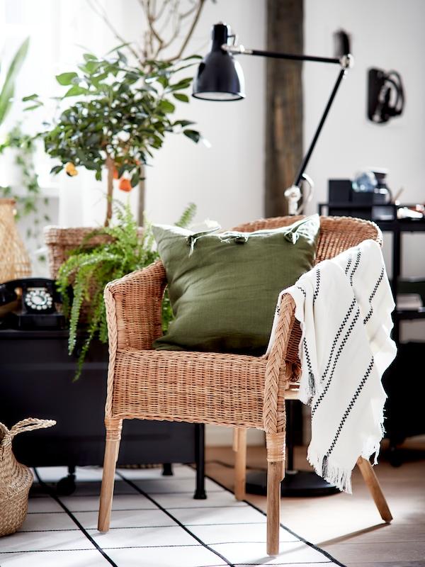 Un scaun din ratan/bambus cu o pernă verde și o pătură în dungi, un covor negru/alb, un lampadar negru și un coș.