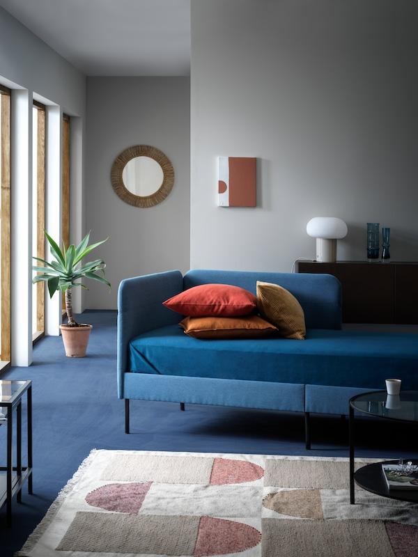 Tapicerowana rama łóżka BLÅKULLEN w dobrze oświetlonym pokoju dziennym w chłodnych barwach, umieszczona w pobliżu dużego dywanika o neutralnej kolorystyce i eleganckiego stolika kawowego.
