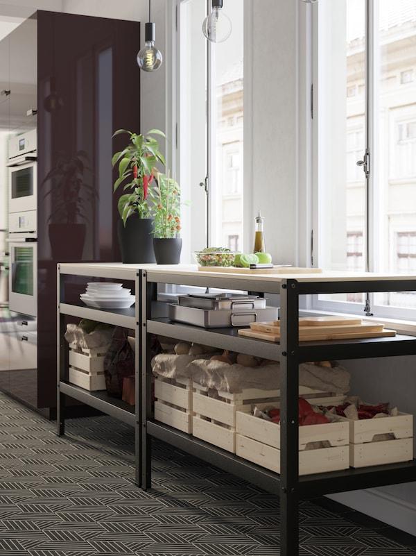 Pored prozora se nalaze dvije radne klupe. Na radnoj ploči nalazi se posuda sa salatom, a na donjim policama stoje razne namirnice.