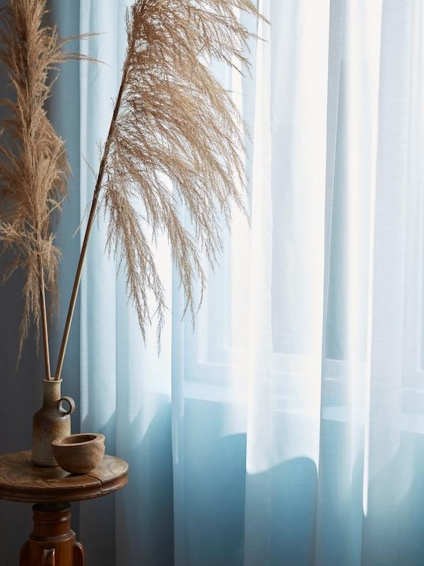Eine GUNRID luftreinigende Gardine hängt vor einem sonnenbestrahlten Fenster neben getrockneten Gräsern in einer Vase.