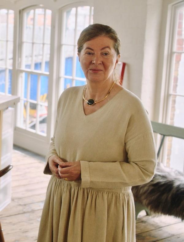 Ilse Crawford egy fehér szobában, bézs ruhát visel, és a kamerába néz.