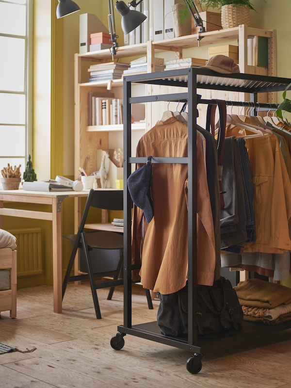 A student room with a black open storage unit on wheels with hanging clothes, and a desk and bookcase in the background.