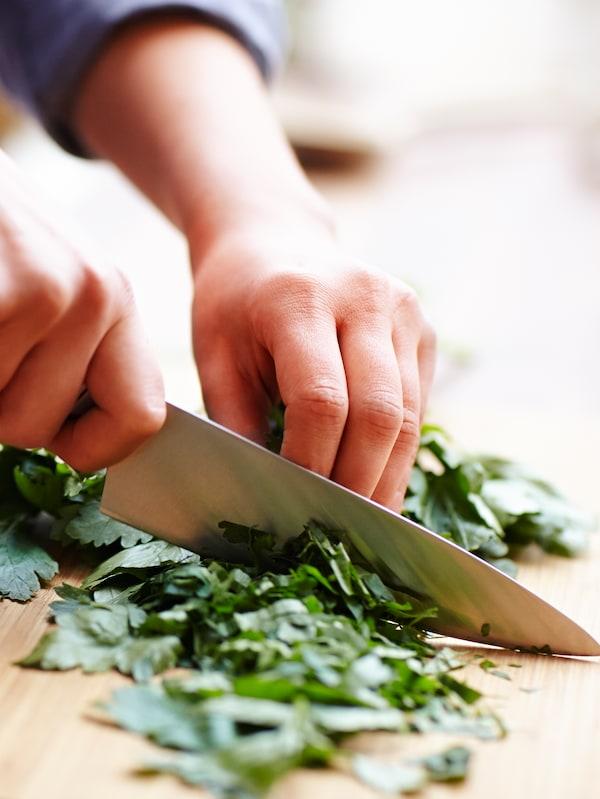 Lähikuva käsistä, jotka pilkkovat vihreitä yrttejä keittiöveitsellä.
