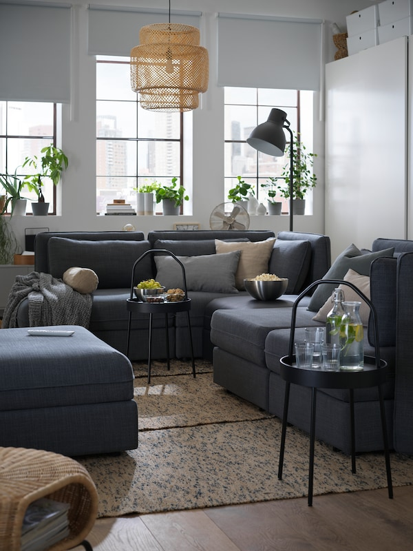 A large VALLENTUNA modular sofa and two black, BURVIK side tables with drinks and snacks, in a one-room apartment.