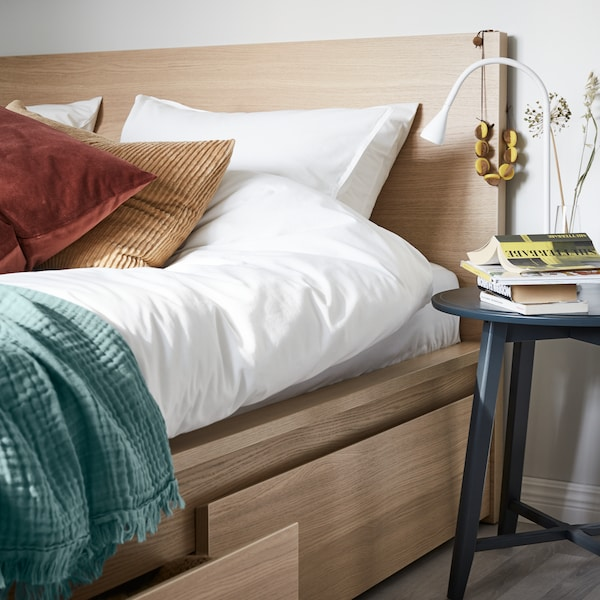 Bed side with a side table which has some books and work lamp