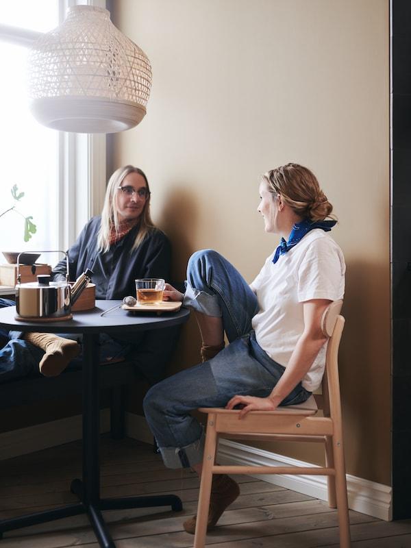 Un couple prend le thé à la table STENSELE, sous une suspension MISTERHULT.