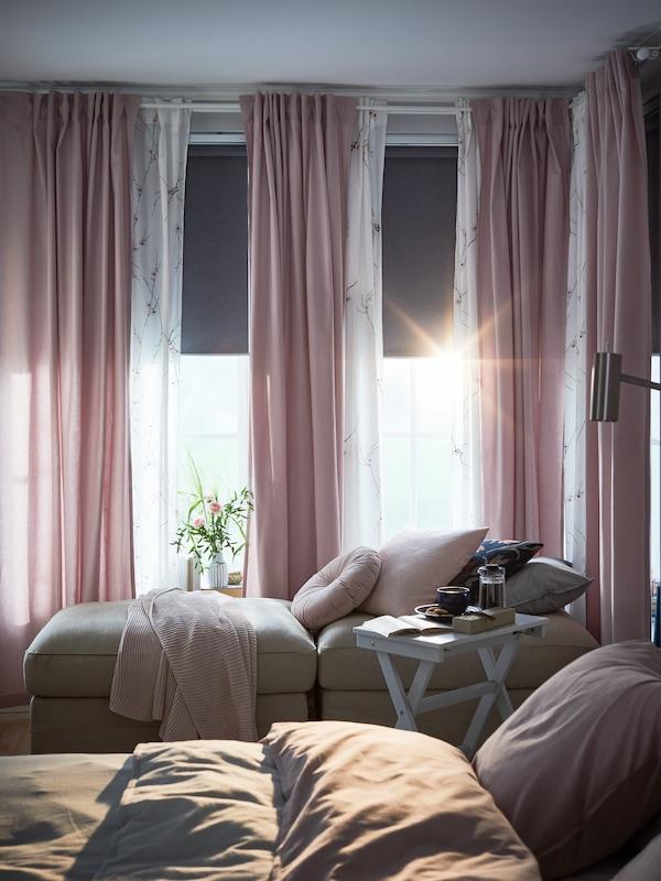 Napfényes hálószoba árnyékolókkal, köztük FYRTUR sötétítő redőnyökkel és  világosrózsaszín KALKFLY függönyökkle.