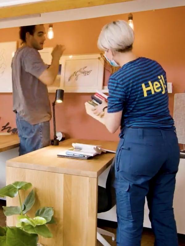 Egy férfi áll egy fa asztal mellett, és egy képet tesz fel a falra, az asztalra pedig egy IKEA munkaruhát viselő nő épp egy stóc könyvet tesz.