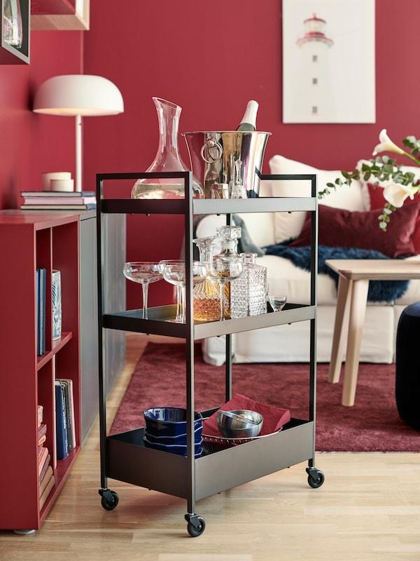 Soggiorno con carrello NISSAFORS in metallo nero usato come mobile bar, con bottiglie, decanter e bicchieri.