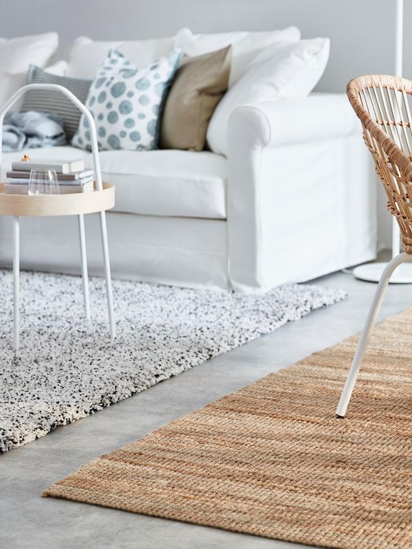 Valkoinen sohva, jolla runsaasti koristetyynyjä. Sohvan edessä vaaleanharmaa karvalankamatto ja kevyt sohvapöytä.