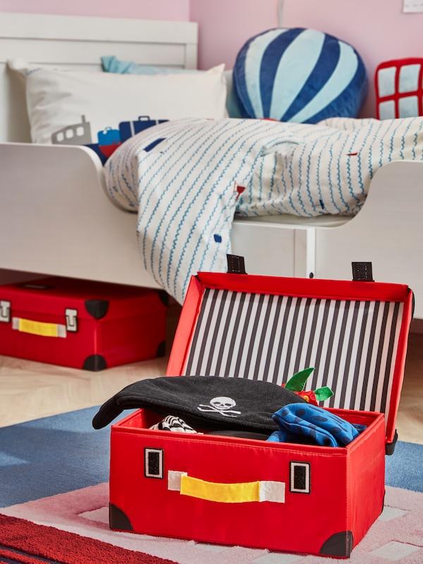 儿童房的地毯上放着红色的FLYTTBAR 福塔 旅行箱,箱子打开,里面装着海盗服。