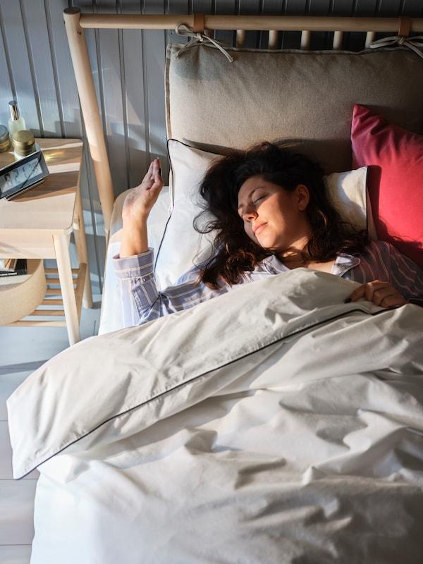Une femme blottie sous une housse de couette KUNGSBLOMMA protège ses yeux des rayons du soleil matinal qui entrent dans la chambre.