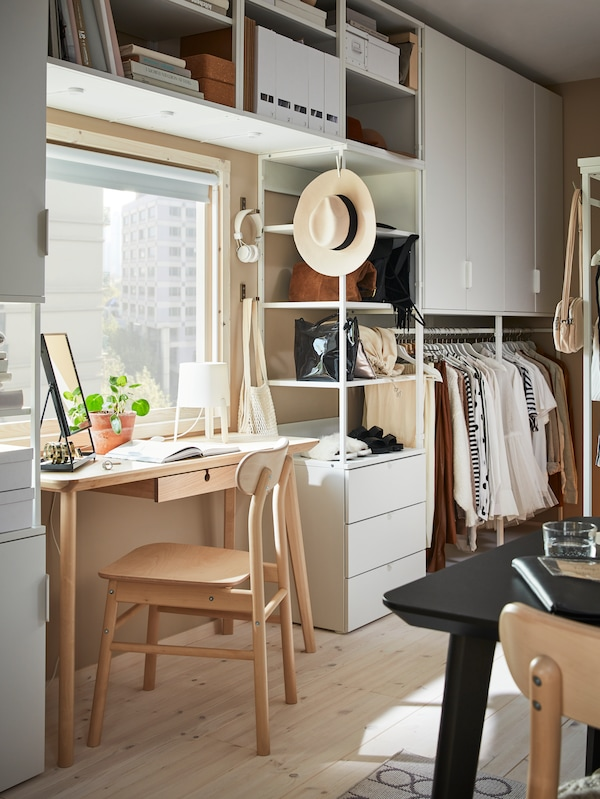 A LISABO desk and a RÖNNINGE chair sit in front of a window with a large PLATSA storage combination mounted on the wall.