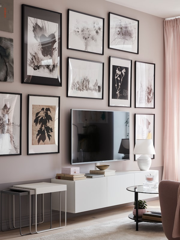 A traditional living room wall, full of pictures with KNOPPÄNG frames in black, behind a TV mounted on a low, white TV bench.