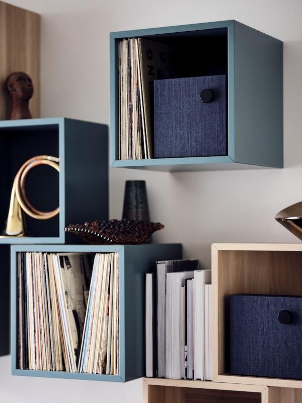 EKET kasser i forskellige farver hængt op på væggen i et vilkårligt mønster.