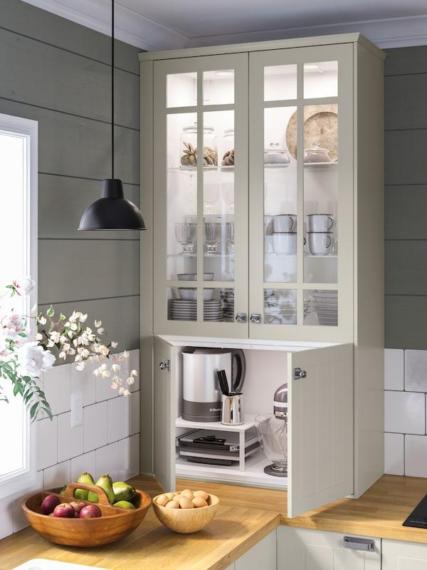 Modernt kök med SINARP lådor och HASSLARP luckor, på bänkskivan står två buketter med röda och rosa blommor.