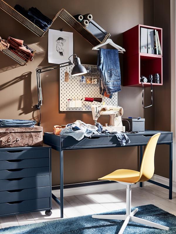 Tmavosivá nástenná pracovná lampa TERTIAL nad šijacím strojom a džínsami a čiernym stolom s tmavožltou otočnou stoličkou.