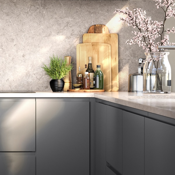 A kitchen with drawers and fronts in dark grey, and a KASKER worktop in marble effect. Condiments neatly placed on top.