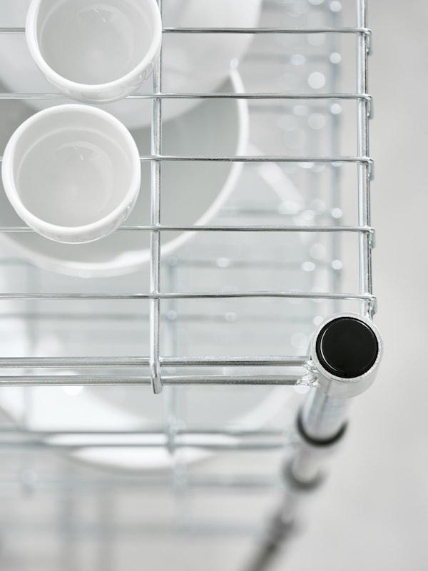 Parte superior de un estante abierto de rejilla de la estantería OMAR; cada estante tiene cuencos blancos de diferentes tamaños.