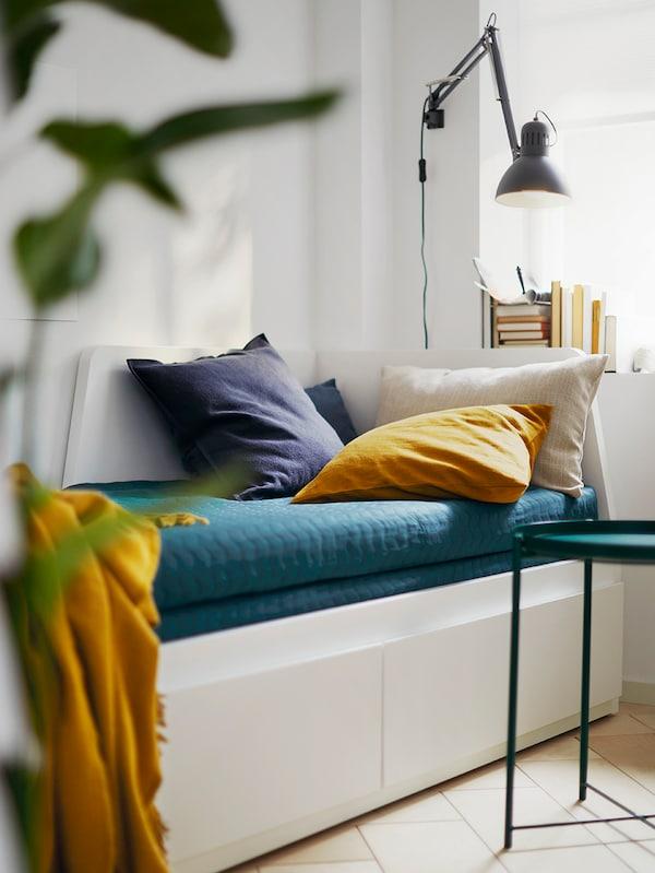 Diván FLEKKE blanco con cojines de color amarillo y azul oscuro y una manta amarilla encima. Detrás, en la pared, hay una lámpara.