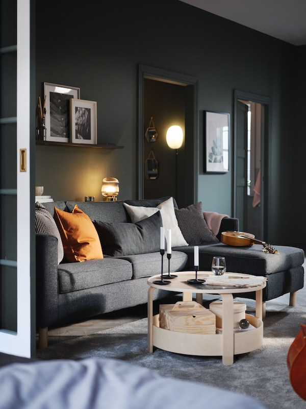 En stue med en grå sofa med chaiselong, gråblå vægge og et rundt sofabord i lyst træ.