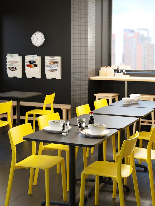 Tavoli STENSELE con sedie JANINGE gialle in una sala ristoro apparecchiati con due piatti bianchi e bicchieri - IKEA