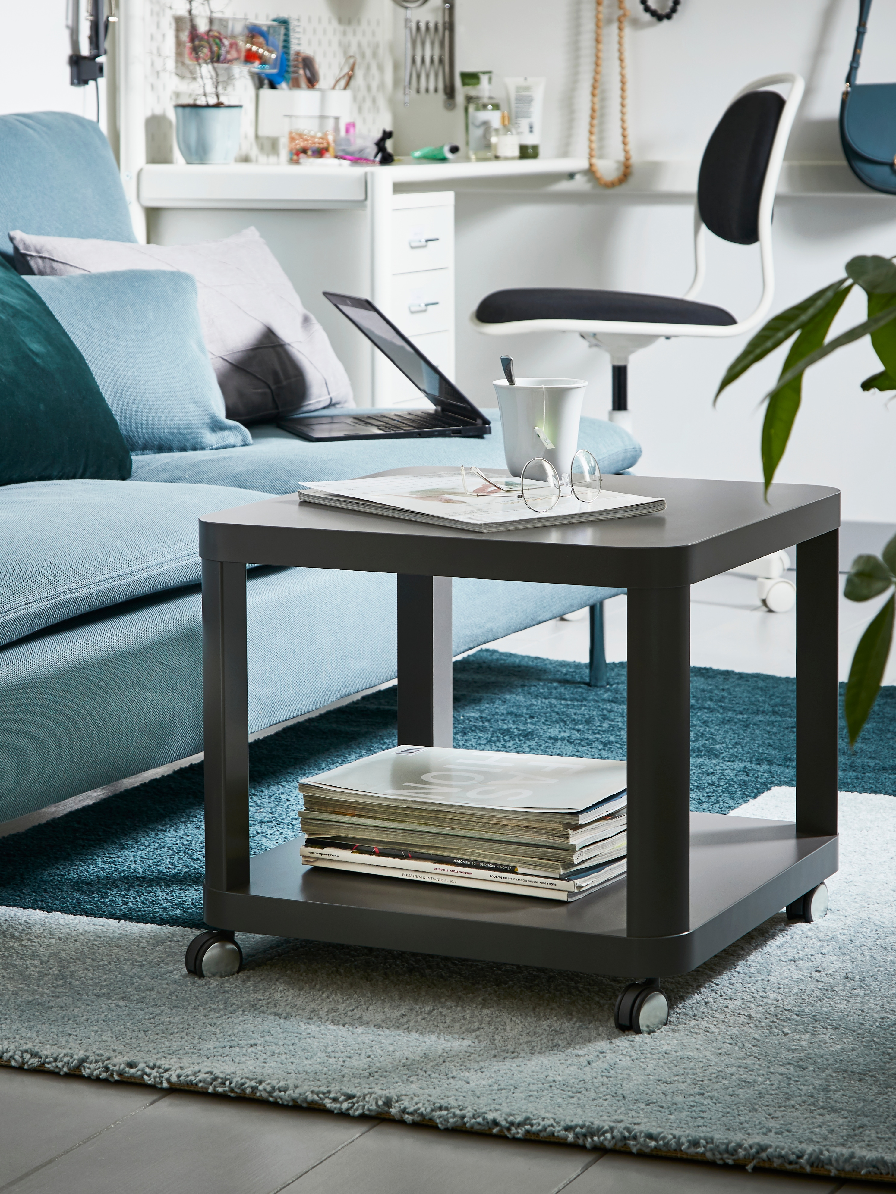 A square, grey TINGBY side table with castors that has a shelf underneath holding magazines on a ru beside a turquoise sofa.