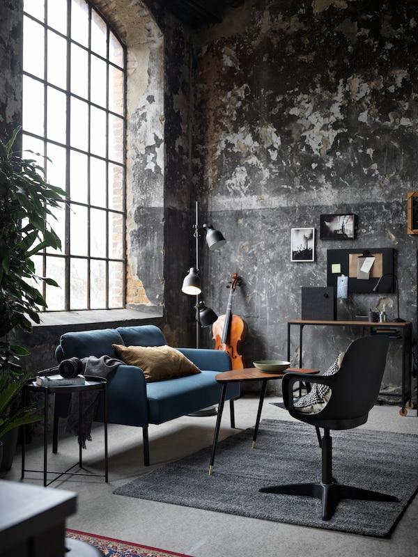 Un canapé 2 places GLOSTAD bleu moyen et une table d'appoint LÖVBACKEN installés sous une grande fenêtre dans une pièce aux murs bruts.