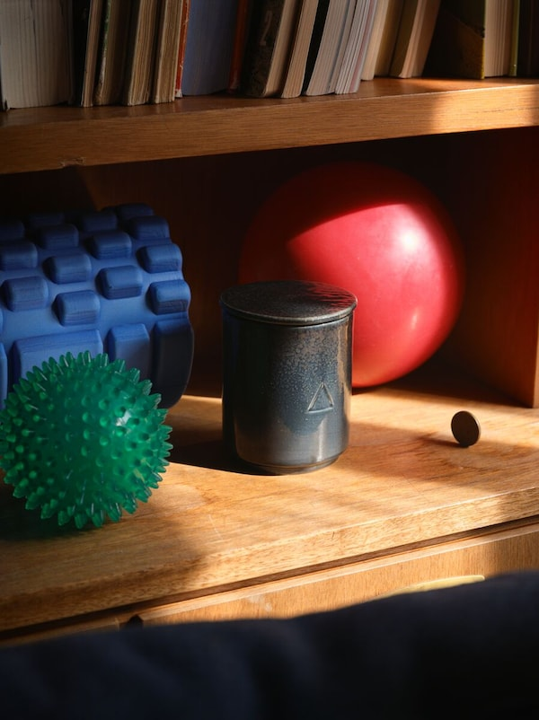 An OSYNLIG scented candle, with its ceramic lid, stands next to exercise equipment on a wooden shelf.