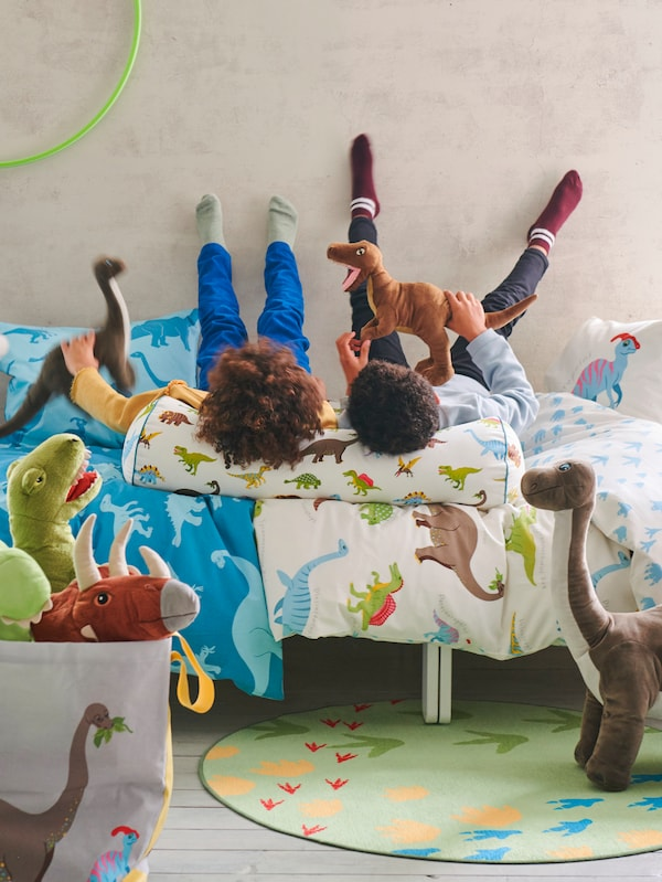 Two children lie on their backs on a bed with JÄTTELIK dinosaur bed linen. They are playing with JÄTTELIK dinosaur soft toys.