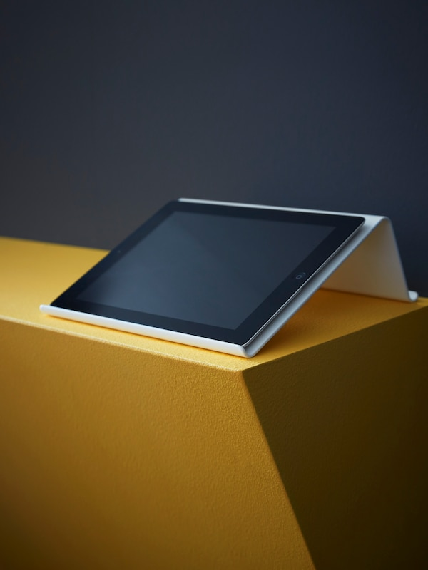 A tablet lies on a white ISBERGET tablet stand which stands on a low wall that has been painted dark yellow.