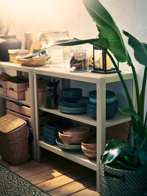 KOLBJÖRN in/outdoor shelving units on a wooden deck are stocked with blue dishware, storage boxes, and other dining products.