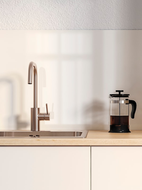 Et blandingsbatteri i stål, en stempelkaffekande på en lys træbordplade og to hvide køkkenlåger.