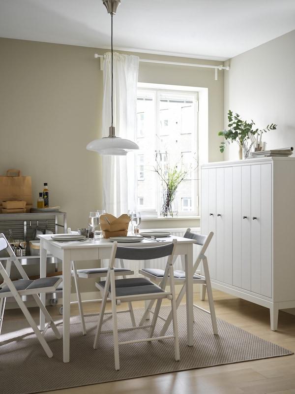 Malý biely jedálenský stôl so štyrmi bielo-svetlosivými stoličkami TERJE. Pri stene stojí skrinka IDANÄS.