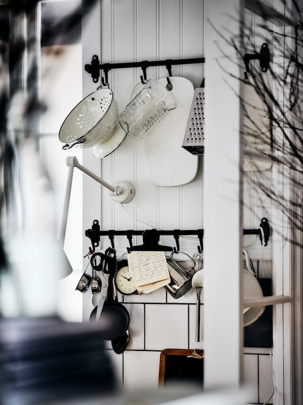 Deux barres support HULTARP noires, sur un mur blanc lambrissé de bois, des ustensiles tels qu'une passoire, une râpe et des pichets suspendus à leurs crochets.