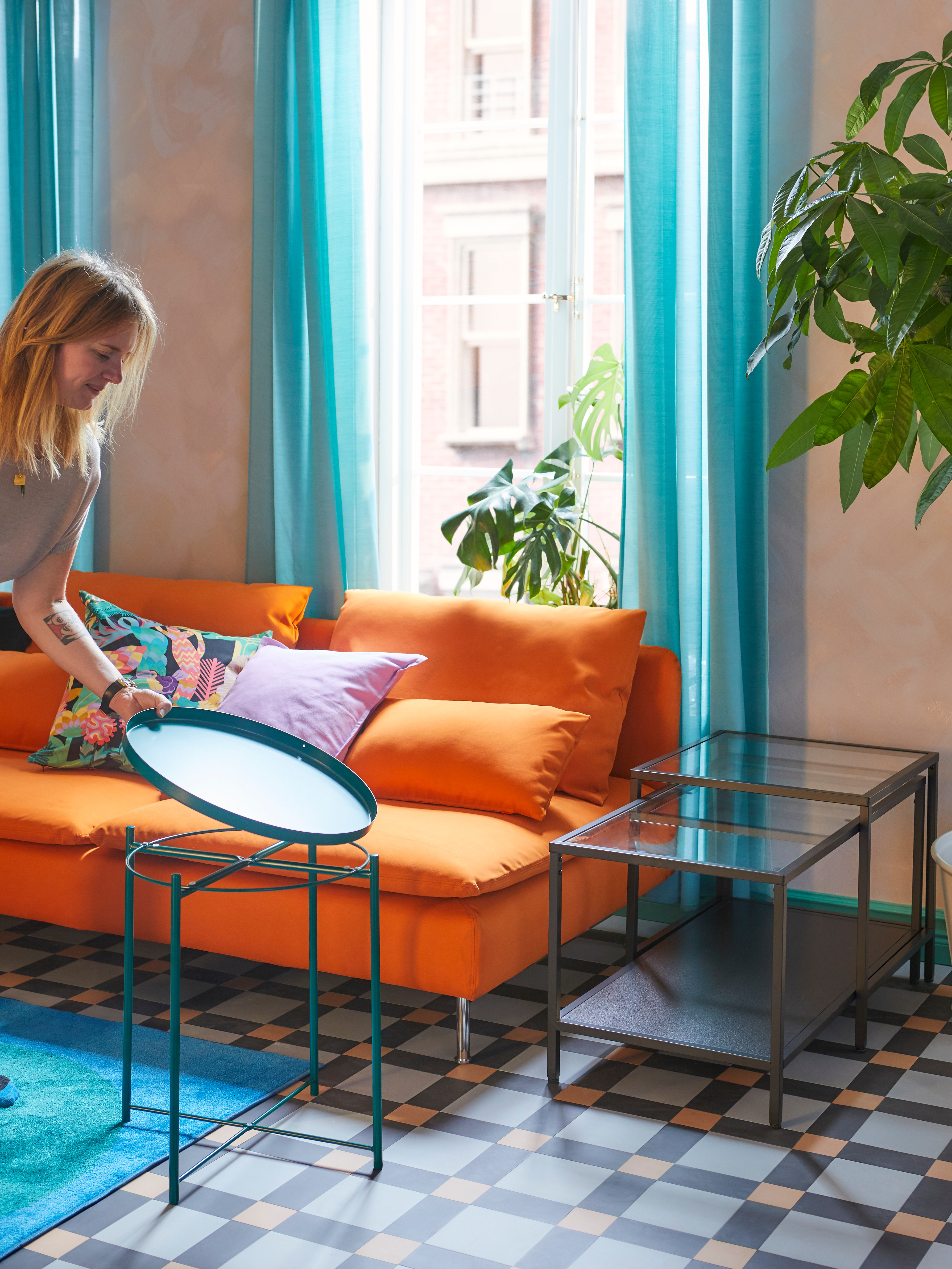 A person lifts the circular tray off a green GLADOM tray table that's near an orange sofa and a nest of tables.