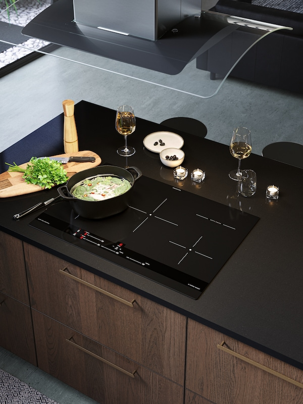 An induction hob on the kitchen island with a black cooking pot and an extractor hood on the ceiling.